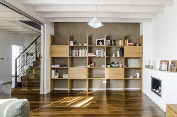 obytný prostor s krbem, knihovnou, trámovým stropem a dřevěnou podlahopu. vše v přírodních materiálech. od jídelny a kuchyně oddělitelné prosklenou posuvnou stěnou.